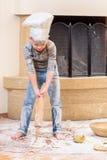 Een jongen in chef-kok` s hoeden dichtbij de open haardzitting op de keukenvloer met bloem wordt bevuild, spelend met voedsel, di stock afbeelding