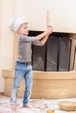 Een jongen in chef-kok` s hoeden dichtbij de open haardzitting op de keukenvloer met bloem wordt bevuild, spelend met voedsel, di stock afbeeldingen