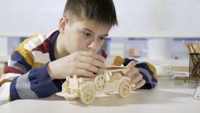 Een jongen construeert een auto van een houten 3d raadsel stock footage