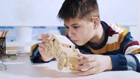 Een jongen construeert een auto van een houten 3d raadsel stock videobeelden