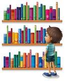 Een jongen in de bibliotheek voor de boekenrekken Royalty-vrije Stock Fotografie