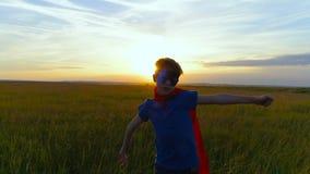 Een jongen in de looppas van een supermankostuum over het groene gebied bij zonsondergang