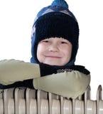 Een jongen dichtbij de radiator van het verwarmen Royalty-vrije Stock Afbeelding