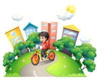 Een jongen die bij de weg biking die naar de hoge gebouwen gaan royalty-vrije illustratie