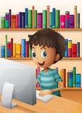 Een jongen die de computer binnen de bibliotheek met behulp van Royalty-vrije Stock Afbeeldingen