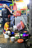 Een jongen die de schotels wassen door de kant van de weg Royalty-vrije Stock Afbeeldingen
