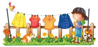Een jongen die in de tuin met het hangen van kleren drinken Royalty-vrije Stock Afbeeldingen