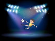 Een jongen die de voetbalbal schoppen in het stadium Stock Fotografie