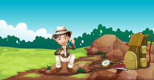 Een jongen die een hoedenzitting op een rots dragen Stock Foto