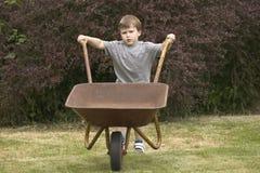 Een jongen die een kruiwagen duwt Stock Foto