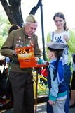 Een jongen die een oorlogsveteraan eren Stock Foto