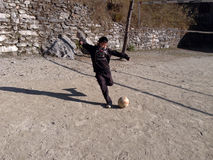 Een jongen die een voetbal schoppen Stock Foto
