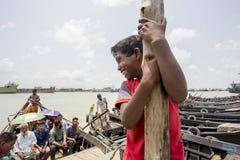 Een jongen die en Karnafuli-tarminal van rivierboten hangen glimlachen Stock Foto