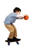 Een jongen die in evenwicht om wordt gehouden om een basketbal te ontspruiten stock foto
