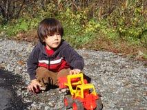 Een jongen die met een plastic stuk speelgoed spelen Stock Afbeelding