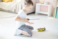 Een jongen die met een verre auto spelen stock fotografie