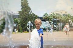 Een jongen die met water in parkfontein spelen De hete zomer stock foto's