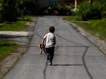 Een jongen die na zijn hond op de betonweg van een kleine straat in een klein slaperig dorp lopen royalty-vrije stock foto