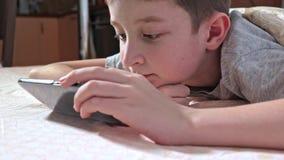 Een jongen die op een bed, het ontspannen en het letten op video op smartphone thuis liggen stock footage