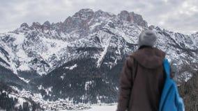 Een jongen die op de bergen letten die met sneeuw worden behandeld stock videobeelden