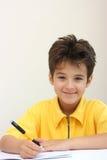 Een jongen die op een oefenboek schrijft Stock Foto's