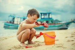 Een jongen die op het strand met zand spelen Royalty-vrije Stock Afbeeldingen