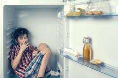 Een jongen die in een overhemd en borrels een chocoladereep binnen een koelkast met voedsel eten stock fotografie