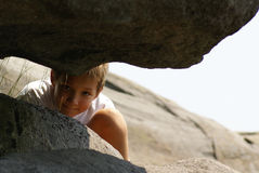 Een jongen die tussen rotsen tuurt Royalty-vrije Stock Afbeeldingen