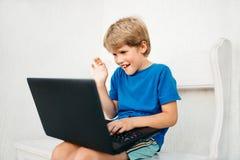 Een jongen die via laptop babbelen Stock Foto