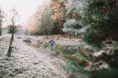 Een jongen die zich door de rivierbank bevinden Het landschap van de winter De winterbos op de rivier royalty-vrije stock foto