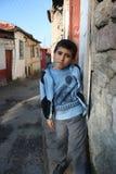 Een jongen die zich voor zijn huis bevindt Stock Foto