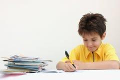 Een jongen die zijn thuiswerk doet Stock Foto