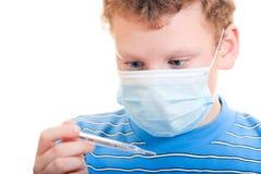 Een jongen in een beschermend masker met in hand thermometer Stock Foto