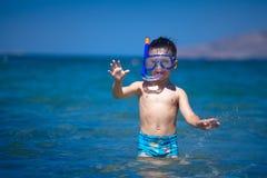 Een jongen in een overzees met het zwemmen maskeert en snorkelt Stock Afbeelding