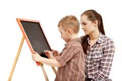 Een jongen, een vrouw en een bord. Het schrijven Stock Foto's