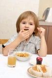 Een jongen eet cracker Stock Afbeeldingen