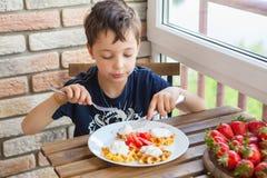 Een jongen eet wafels met aardbeien Royalty-vrije Stock Fotografie