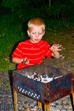 Een jongen en een brand Stock Foto's