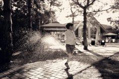 Een jongen en een nevel van water Stock Afbeeldingen