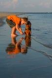 Een jongen en een puppy door het strand Stock Foto's