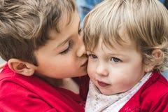 Een jongen en een meisje, broers, die elkaar kussen royalty-vrije stock foto's