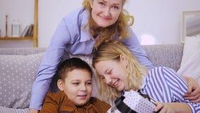 Een jongen en een meisje lezen een boek en ontvangen giften van hun moeder stock footage