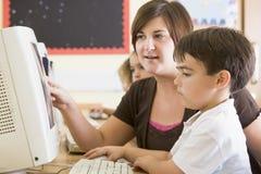 Een jongen en zijn leraar die aan een computer werken stock foto