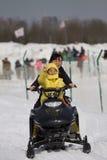 Een jongen en zijn moeder berijden een sneeuwmotorfiets Royalty-vrije Stock Foto