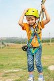 Een jongen in een gele helm houdt op de kabel en onderzoekt de camera op de kabelwagen in een extreem park stock foto's