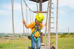 Een jongen in een gele helm overwint een hindernis op de kabelwagen in een extreem park stock afbeeldingen