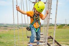 Een jongen in een gele helm overwint een hindernis op de kabelwagen in een extreem park royalty-vrije stock foto