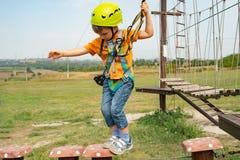 Een jongen in een gele helm overwint een hindernis op de kabelwagen in een extreem park stock fotografie