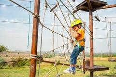 Een jongen in een gele helm overwint een hindernis op de kabelwagen in een extreem park royalty-vrije stock fotografie