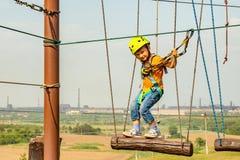 Een jongen in een gele helm overwint een hindernis op de kabelwagen in een extreem park stock afbeelding